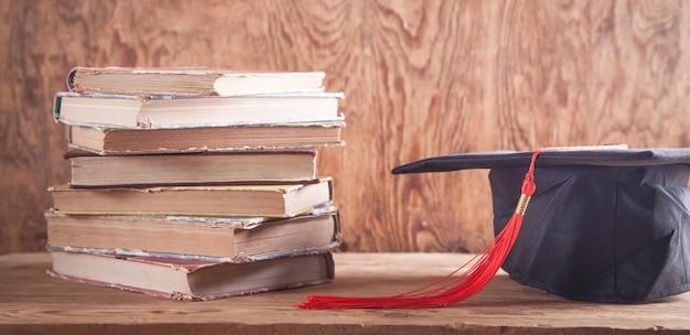 Кепка с книгами на деревянном столе. образование