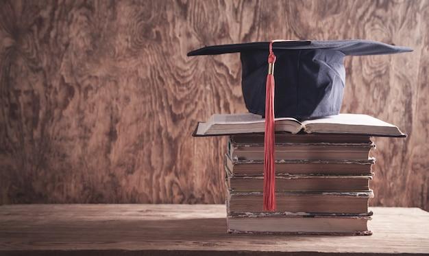 Кепка выпускного вечера с книгами на деревянном столе. образование