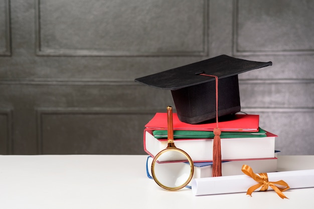 Graduation cap with books on white desk , education background