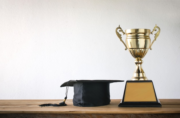 Graduation cap with champion golden trophy on wood table