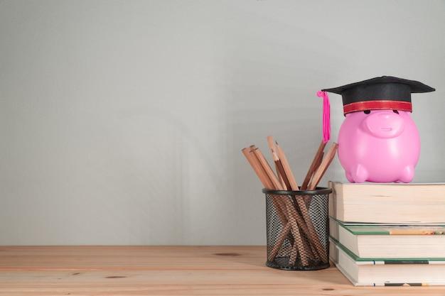 Graduation cap with piggy bank on books.