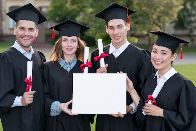 Graduation concept with students holding blank certificate template