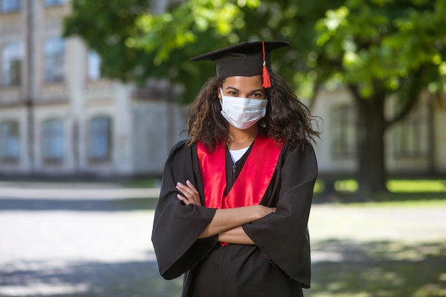 Graduation a darkskinned girl in academic gown and in preventive mask