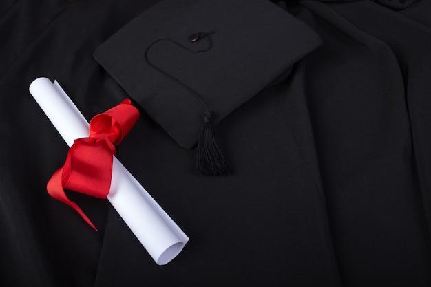 卒業の日。ガウン、卒業帽、卒業証書、卒業式の準備ができてレイアウトされています。