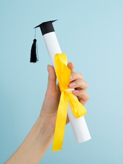 Graduation diploma with yellow ribbon and academic cap