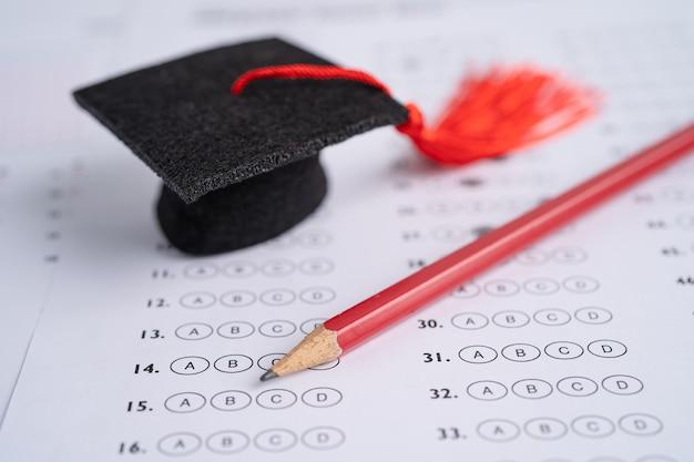 답안지 배경 교육 개념에 졸업 갭 모자와 연필