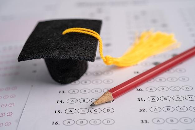 Выпускной пробел шляпа и карандаш на фоне листа ответов