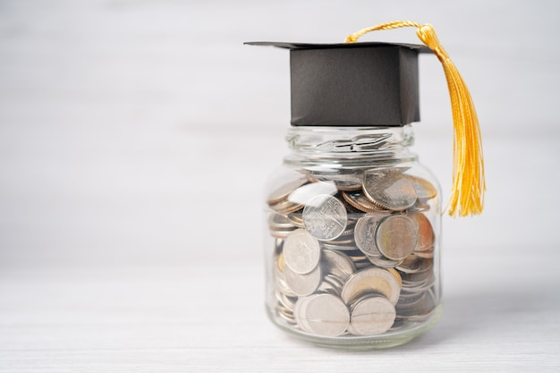 Graduation gap hat on coins money in jar for education fund.