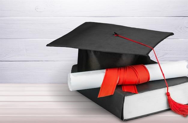 木製のテーブルに卒業式の帽子、本、卒業証書