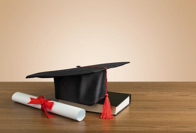 나무 테이블에 졸업 모자, 책 및 졸업장