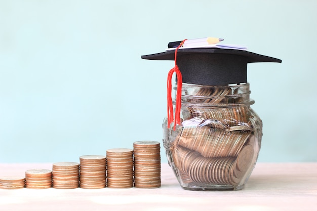 Graduation hat on coins money in the glass bottle on white background