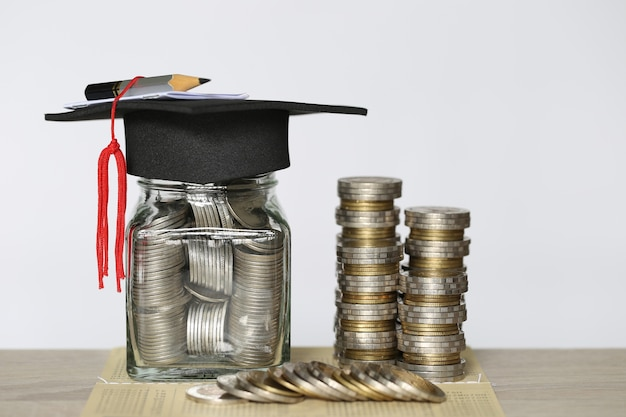 Graduation hat on the glass bottle with stack of coins money on wtite