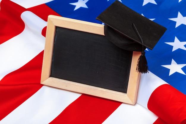 Graduation hat mortarboard on us flag, education concept