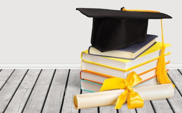 책과 졸업장의 스택에 졸업 모자