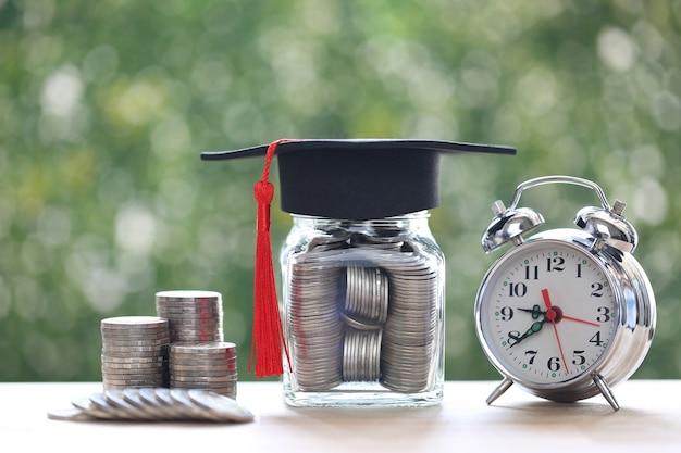 Выпускная шляпа на стеклянной бутылке и будильник на естественном зеленом фоне, концепция экономии денег на образование