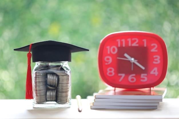 ガラス瓶の卒業帽子と自然な緑の背景の目覚まし時計、教育コンセプトのためのお金を節約