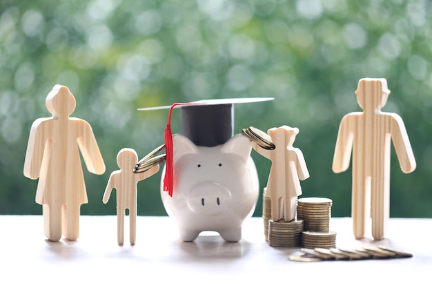 Graduation hat on piggy bank with model family and stack of coins money on natural green background