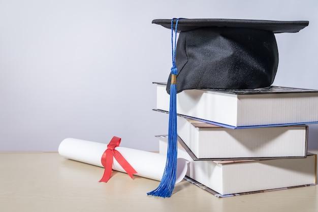 흰색 backgrou에 대 한 테이블에 책과 졸업장 졸업 모자