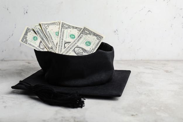 テーブルの上のお金と卒業帽子。授業料の概念