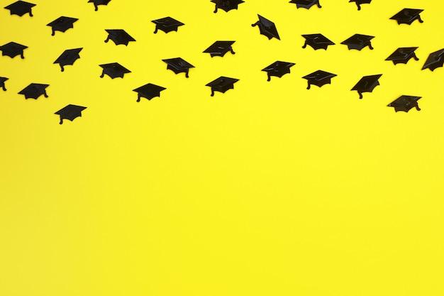 Graduation hats confetti on yellow background celebration background