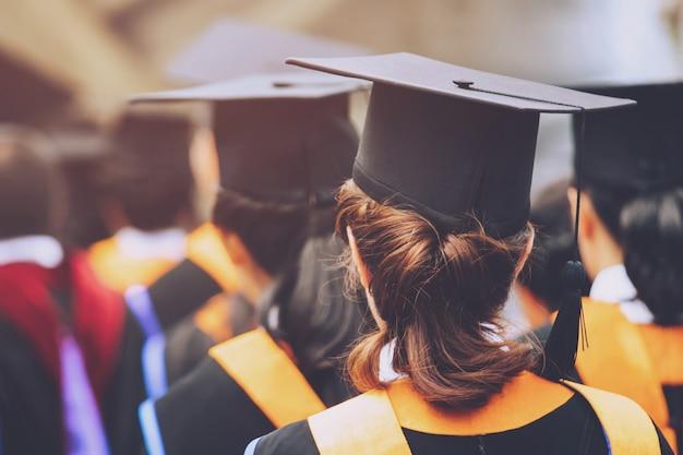 卒業、学生は大学の開始成功卒業生の間に帽子を手に持って、概念教育おめでとう