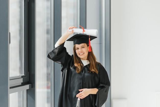 卒業:卒業証書を持って立っている学生
