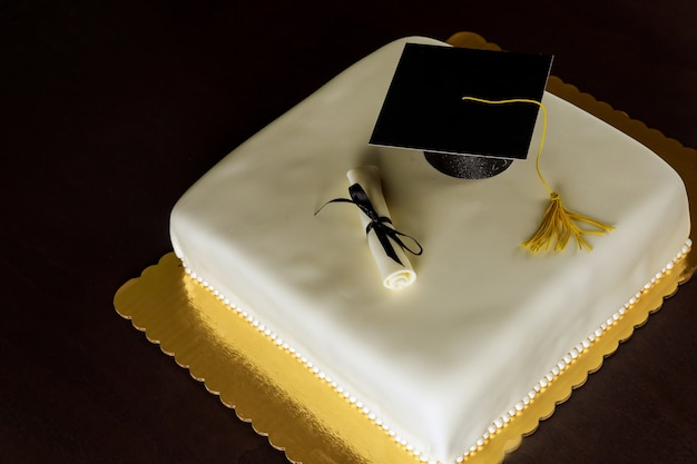 上部にキャップと卒業証書の装飾が施された卒業式の白いケーキ。