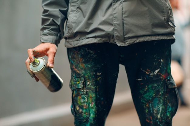 Graffiti artist in clothes stained with paint spray can in hand
