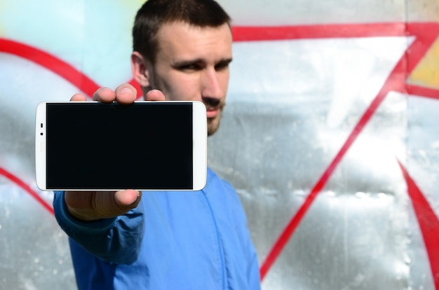 The graffiti artist demonstrates a smartphone with an empty