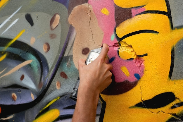 Художник-граффити рисует на стене