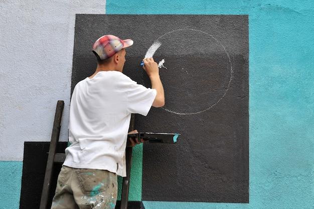 Graffiti artist paints colorful graffiti on a concrete wall modern art urban concept