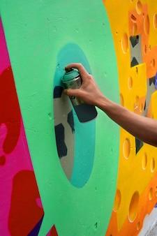 낙서 예술가는 콘크리트 벽에 다채로운 낙서를 그립니다. 현대 미술, 도시 개념.