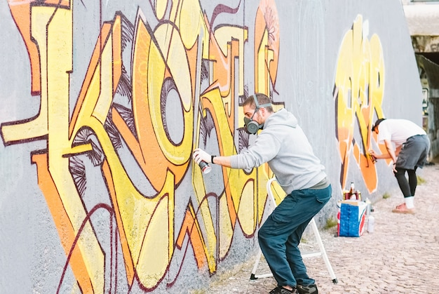 Graffiti artists painting colorful mural on a grey wall