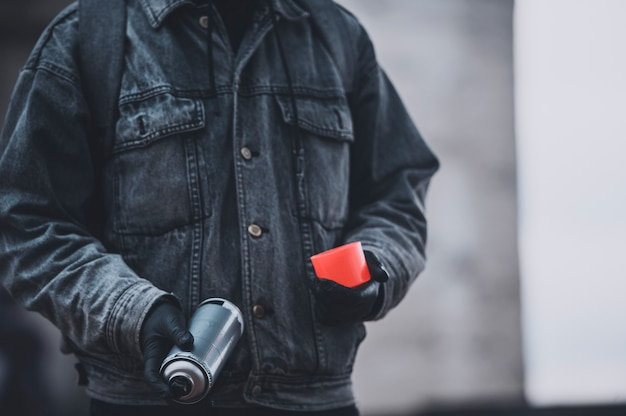 スプレーペイント缶付きデニムコートのグラフィティスト。仕事の準備