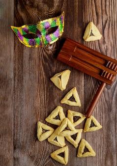 Грэггер с карнавальной маской на деревянных фоне. еврейский праздник пурим.