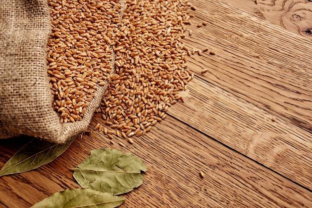 Мешок для зерна на деревянном столе, сельское хозяйство, ингредиент здоровой пищи