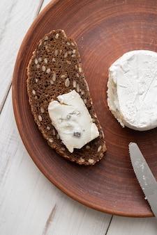 갈색 점토 접시에 곡물 빵과 블루 치즈. 요리 간식. 프리미엄 사진