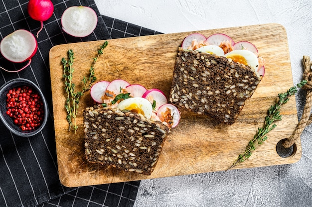 Grain bread sandwiches with hot smoked salmon, eggs and radishes. healthy balanced food. gray surface, top view.