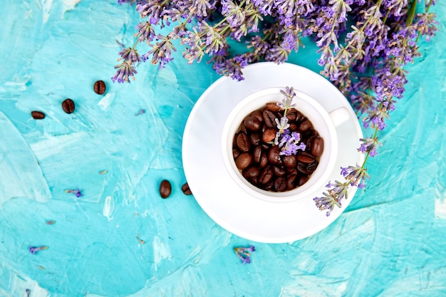 Grain coffee in cups and lavender flower on blue background from above.