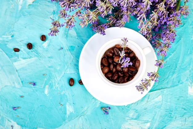 Зерновой кофе в чашках и цветок лаванды на синем фоне сверху.
