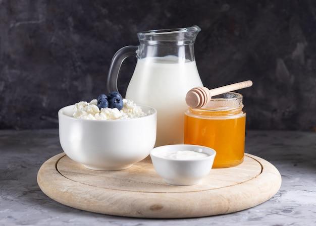 Зерновой творог в белой миске с молочником на светлом фоне
