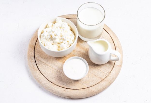 Grain cottage cheese in a white bowl with a milk jug on a light background