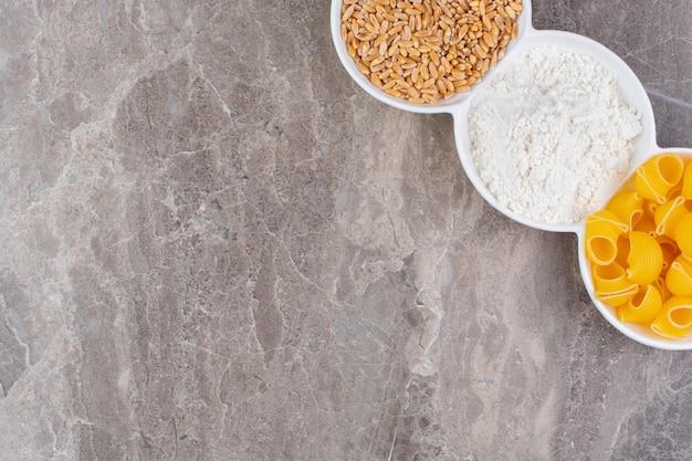대리석 표면에 그릇에 곡물, 밀가루 및 파스타