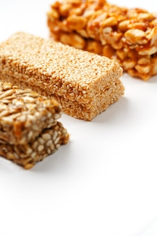 Grain granola bar with peanuts, sesame and seeds in a row. top view three assorted bars, isolate