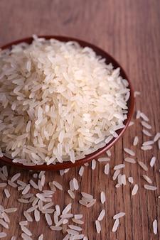 Зерна риса на тарелке на деревянных фоне