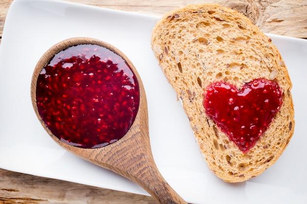 Ломтик зерна хлеба с формой сердца варенья.