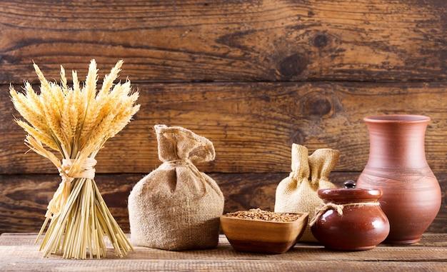 木製の背景に穀物と小麦の耳