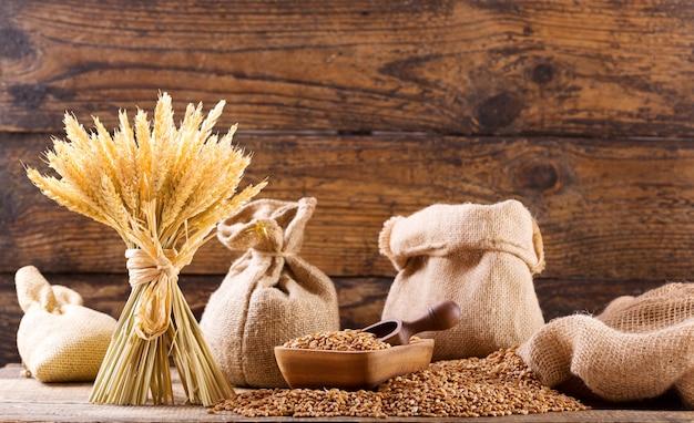 木製のテーブルの上の穀物と小麦の穂