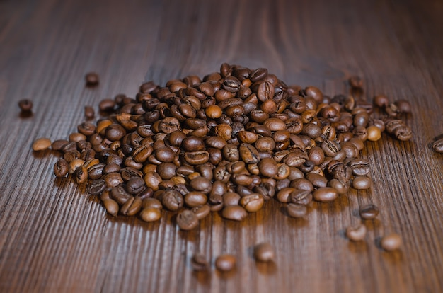 Grains of black coffee lie on a wooden table.