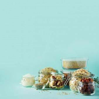 Grains, cereals, nut, dry fruits in glass jars over blue background with copy space.